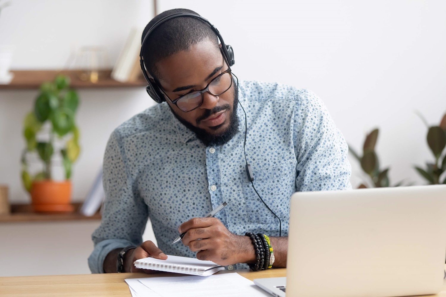 Man with headphones studying on laptop