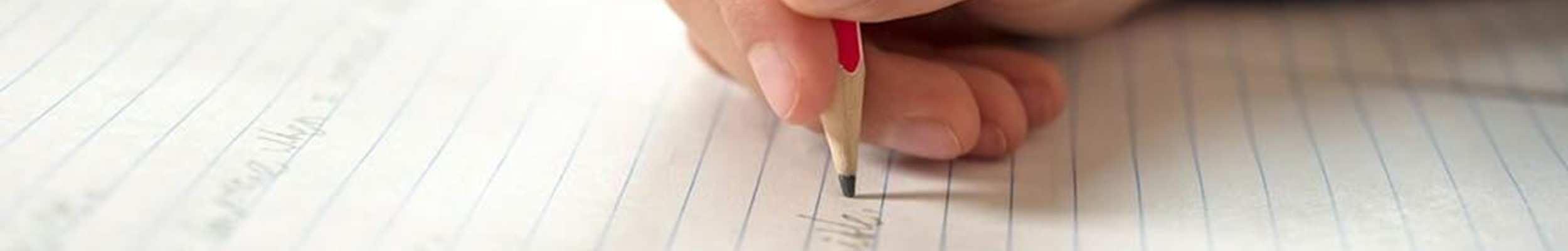 Writing on lined paper with a pencil